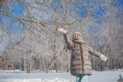 Little girl in grey jacket plays in winter forest in sunny day Stock Images