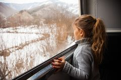 Little girl in grey sweater travelling by Kukushka train in Georgia and looking throught the window royalty free stock images