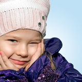 Little girl grimaces. Five years' girl in a knitted beret winks Stock Image