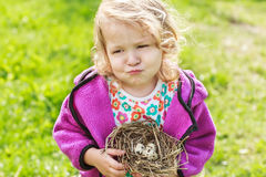Little girl grimacing and holding nest with eggs Stock Photography