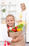 Little girl with the groceries bag Stock Photos
