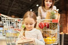 Little Girl Grocery Shopping with Mom. Warm-toned portrait of family doing grocery shopping in supermarket, focus on little girl holding shopping list standing royalty free stock images