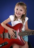 Little girl and guitar. Little girl playing with red electric guitar and singing Royalty Free Stock Photo