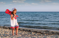 Little girl with guitar on beach Royalty Free Stock Image
