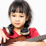 Little girl on guitar and headphone Royalty Free Stock Photography