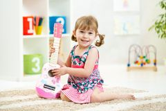 Little girl with guitar toy gift. Siiting on floor Stock Photo