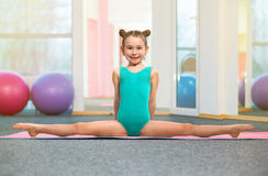 Little girl gymnast sitting in the cross split in gym Royalty Free Stock Images