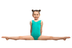 Little girl gymnast sitting in the splits. Isolated on white