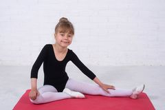 A little girl in a gymnastic swimsuit performing exercises, free space. The girl trains in the studio dance ballet cute leotard making movement new kid child royalty free stock photos