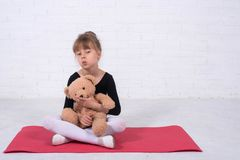 Little girl in the gymnastic swimsuit and with a teddy bear, free space. The girl trains in the studio dance ballet cute leotard making movement new kid royalty free stock photo