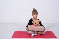 Little girl in the gymnastic swimsuit and with a teddy bear, free space. The girl trains in the studio dance ballet cute leotard making movement new kid stock photography
