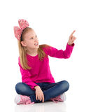 Little girl with hair bow pointing Royalty Free Stock Photography