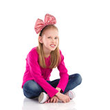 Little girl with hair bow sitting with legs crosse Royalty Free Stock Photo