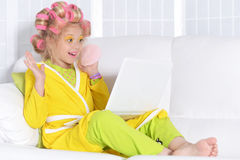 Little girl in hair curlers and laptop Royalty Free Stock Images