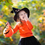 Little girl on Halloween trick or treat. Little girl in witch costume playing in autumn park. Child having fun at Halloween trick or treat. Kids trick or Royalty Free Stock Images