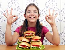 Little girl with hamburgers and ok hand signs Stock Image