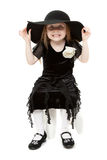 The little girl hamming in a black felt hat Royalty Free Stock Image