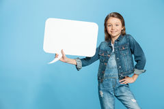 Little girl with hand on hip holding speech bubble on blue. Smiling little girl with hand on hip holding speech bubble on blue Royalty Free Stock Image