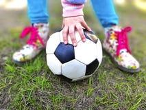 Little girl hand hold soccer ball on green grass. stock photo