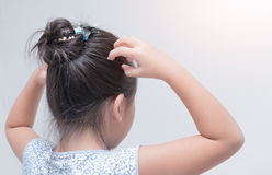Little girl hand itchy scalp. Little girl hand itchy scalp on gray background, Hair care concept stock images