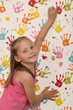 Little girl and hand prints. Little girl on a background wallpaper with children colored hand prints royalty free stock images
