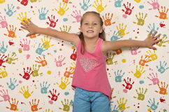 Little girl and hand prints. Little girl on a background wallpaper with children colored hand prints stock photography
