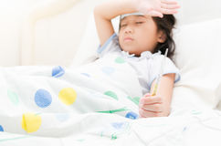 Little girl hand with a thermometer. Hand with a thermometer, sick child girl lying in bed and touch her forehead Stock Images