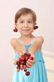 Little girl with handful of cherries. Little girl offerinf a handful of cherries stock image