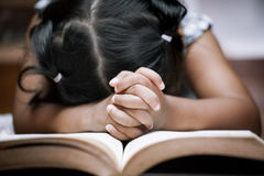 Little girl hands folded in prayer on a Holy Bible Stock Image