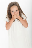 Little girl with hands on her mouth Stock Images