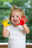 Little girl with hands painted Stock Images
