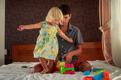 little girl hands sideward stands by father on sofa Royalty Free Stock Images