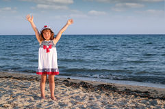 Little girl with hands up on beach Royalty Free Stock Photography