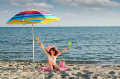 Little girl with hands up sitting under sunshade on beach Stock Photos
