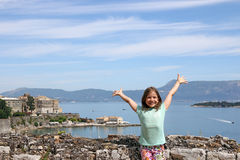 Little girl with hands up on summer vacation Corfu town Stock Photo