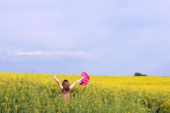Little girl with hands up in yellow field. Summer season Stock Photography