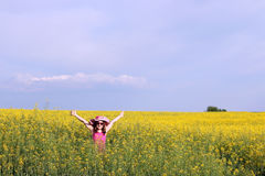 Little girl with hands up on yellow flower field Stock Images