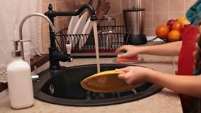 Little girl hands washing a plate at the kitchen sink stock video footage