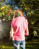 Little girl hanged by clothespins on rope Royalty Free Stock Image