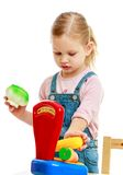 Little girl hanging in the balance fruit . Stock Photos