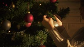 Little girl hanging ball on Christmas tree, decorating before holiday, tradition stock video footage