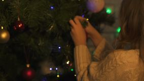 Little girl hanging Christmas tree toy, decoration for festive season, closeup