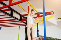 Little girl hanging on the crossbar, mom supports. In the gym royalty free stock images