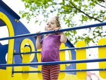 Little girl hanging on the crossbar on the playground. Close-up stock photos