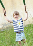 Little girl hanging on gymnastic rings outside Stock Photos