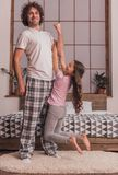 Dad and daughter. Little girl is hanging on her handsome dad`s arm, he is looking at camera and smiling while they are playing together at home royalty free stock photography