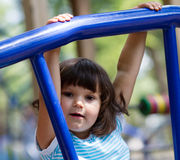 Little girl hanging on a playground Royalty Free Stock Photo
