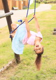 Little girl hanging on rope Stock Image