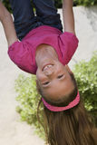 Little Girl Hanging Upside Down. Portrait of a cheerful young girl hanging upside down on a swing Stock Photo