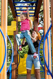 Little girl hangs by horizontal bar Royalty Free Stock Photos